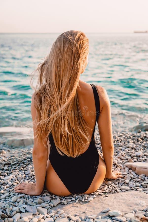 Mujer rubia en bikini del traje de baño con puesta del sol del verano fotos de archivo libres de regalías