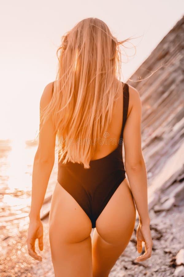 Mujer rubia en bikini negro en la playa con colores de la puesta del sol del verano fotos de archivo libres de regalías