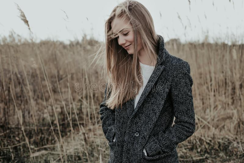 Mujer rubia en capa de las lanas en el prado foto de archivo