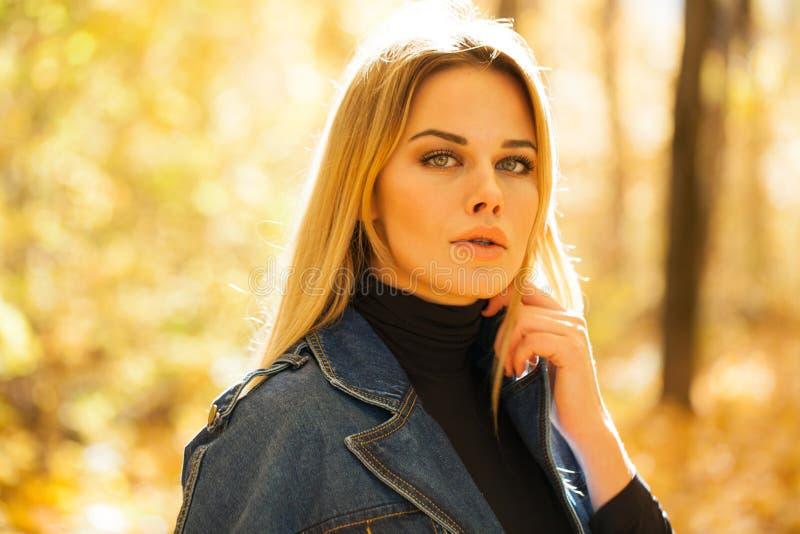 Mujer rubia en el guardapolvo azul del dril de algodón que presenta en el parque del otoño foto de archivo libre de regalías