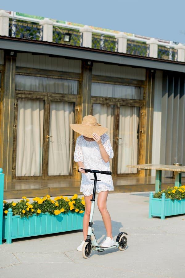 Mujer rubia en el vestido y el sombrero blancos en el montar a caballo azul de la vespa del retroceso en el camino fotos de archivo libres de regalías