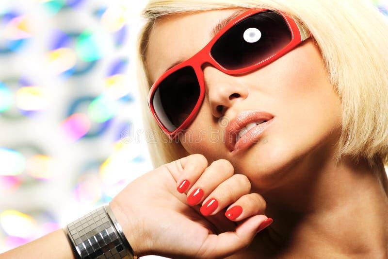 Mujer rubia en gafas de sol rojas imagen de archivo