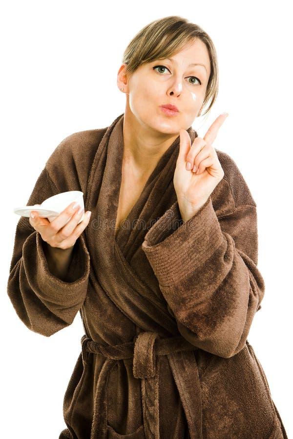 Mujer rubia en la bata marrón de gran tamaño grande que aplica la cara imagen de archivo