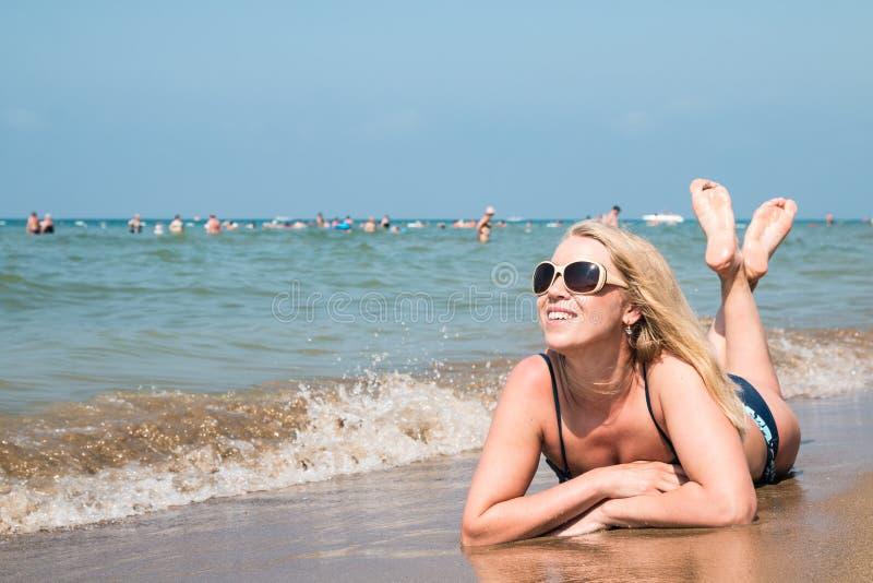 Mujer rubia en la playa en un agua del mar fotografía de archivo