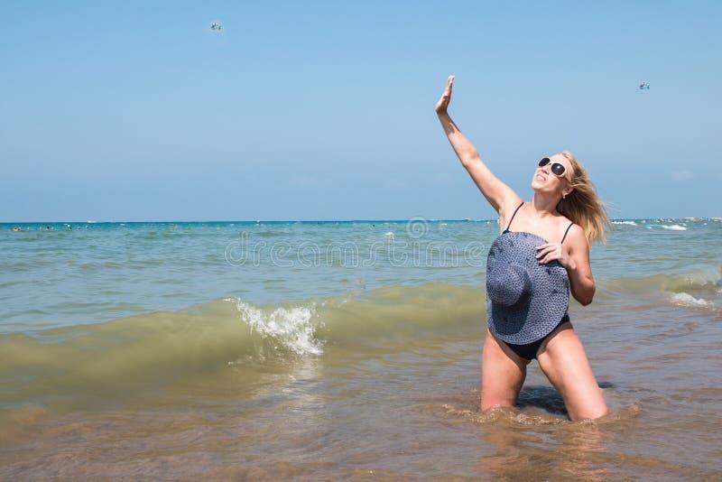 Mujer rubia en la playa en un agua del mar foto de archivo