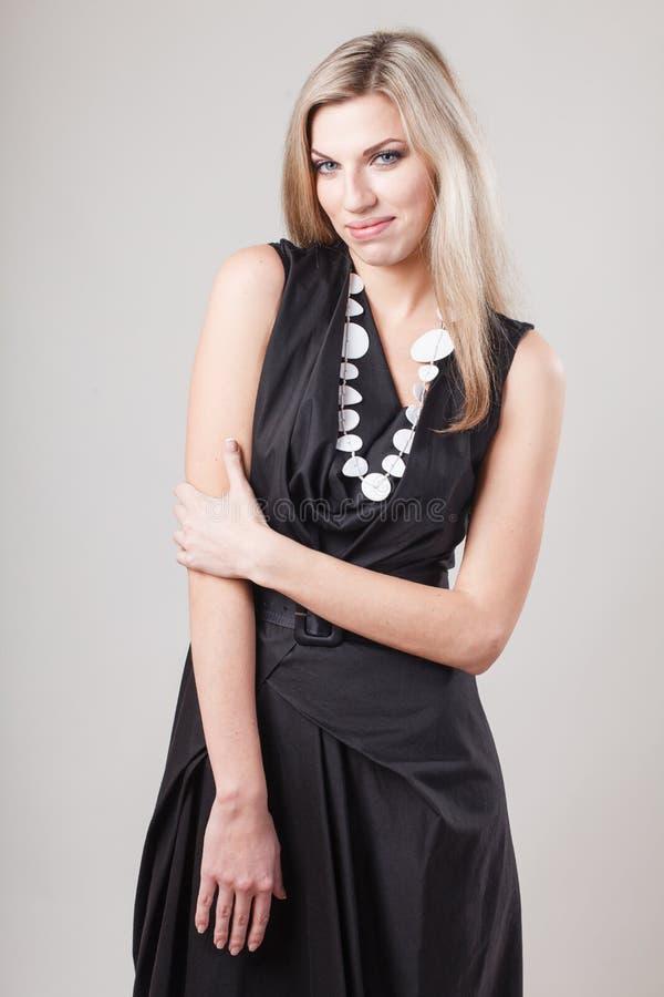 Mujer rubia en poco vestido negro de la moda imágenes de archivo libres de regalías