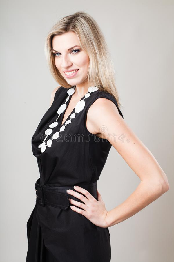 Mujer rubia en poco vestido negro de la moda fotos de archivo libres de regalías