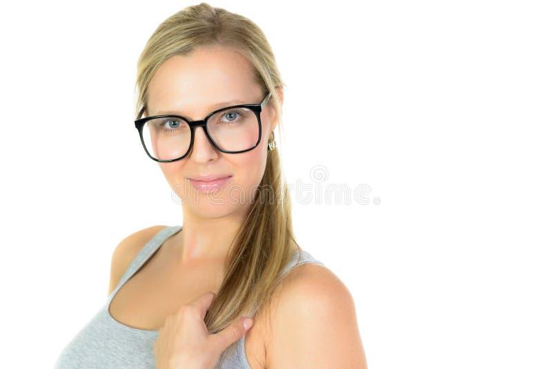 Mujer rubia en sonrisas de los vidrios foto de archivo libre de regalías