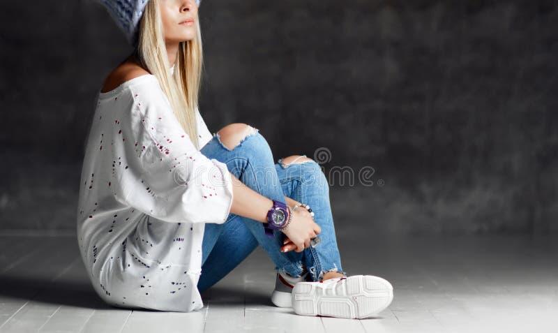 Mujer rubia en vaqueros hechos punto azules claros del sombrero y la sentada sonriente feliz de la camiseta blanca en piso de mad fotos de archivo libres de regalías