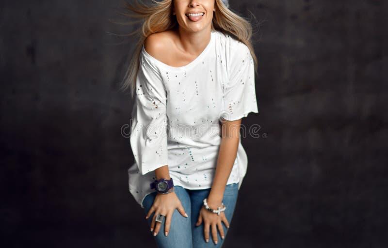 Mujer rubia en vaqueros hechos punto azules claros del sombrero y la sentada sonriente feliz de la camiseta blanca en piso de mad imágenes de archivo libres de regalías