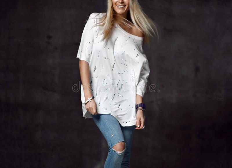 Mujer rubia en vaqueros hechos punto azules claros del sombrero y la sentada sonriente feliz de la camiseta blanca en piso de mad foto de archivo
