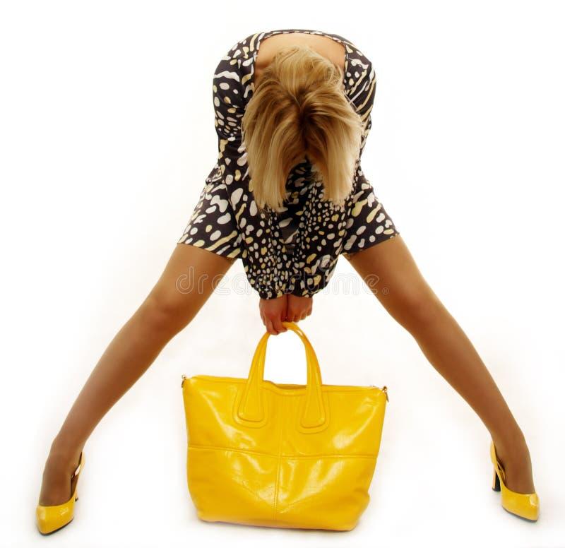 Mujer rubia encantadora con el bolso amarillo imagenes de archivo