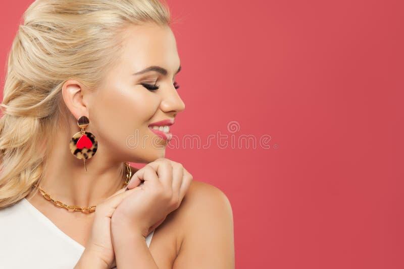 Mujer rubia feliz con el pendiente de oro de la moda en el fondo rosado colorido, retrato del perfil imagenes de archivo