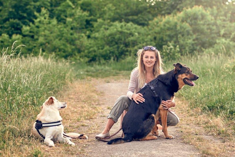 Mujer rubia feliz con sus dos perros leales que toman un resto fotografía de archivo libre de regalías
