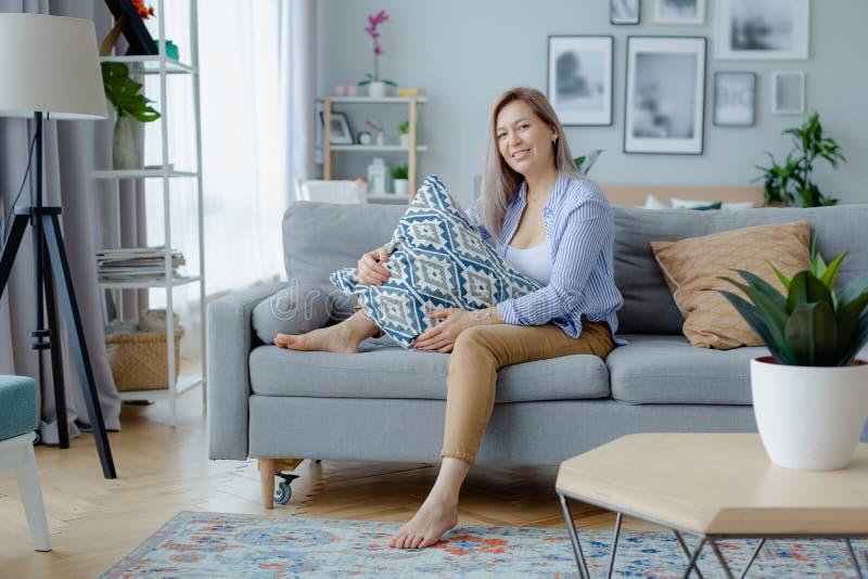 Mujer rubia feliz joven en interior acogedor foto de archivo