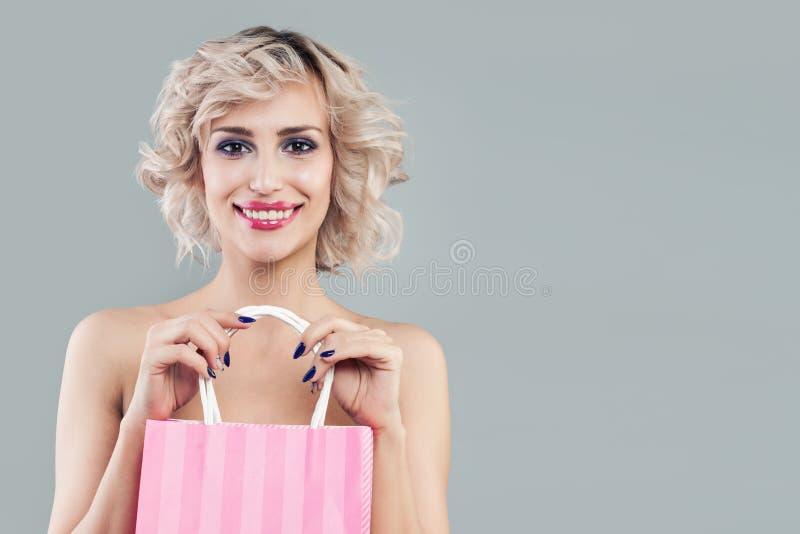 Mujer rubia feliz que celebra bolsos que hacen compras rosados y la sonrisa fotografía de archivo libre de regalías