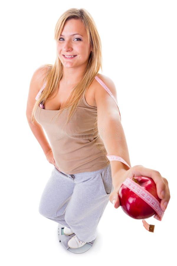 Mujer rubia feliz que detiene la manzana y a la cinta métrica imagenes de archivo