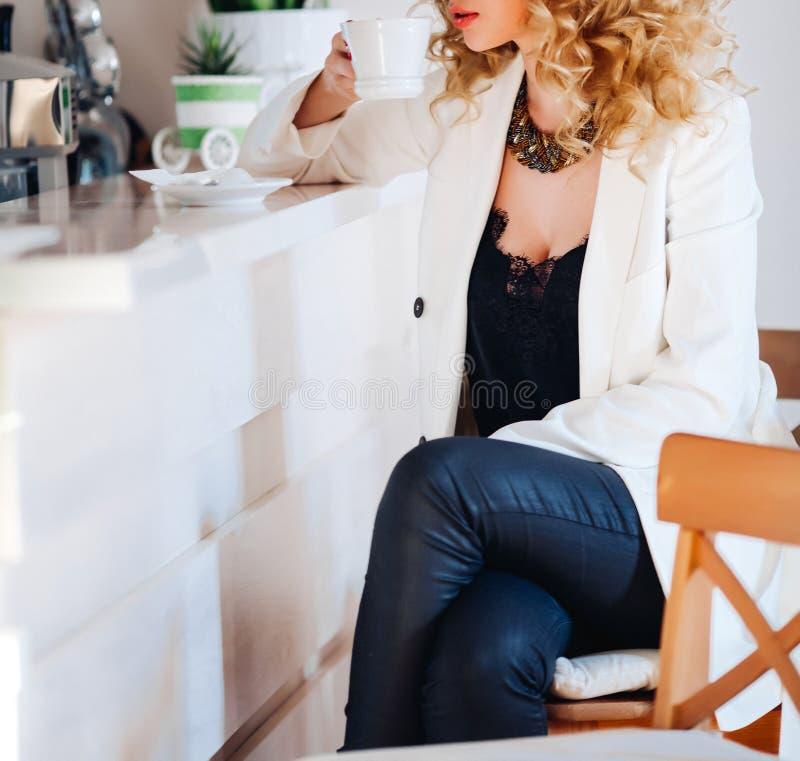 Mujer rubia feliz que se sienta en café del aire libre Maquillaje brillante, labios rojos, fondo moderno de la ciudad imagen de archivo libre de regalías