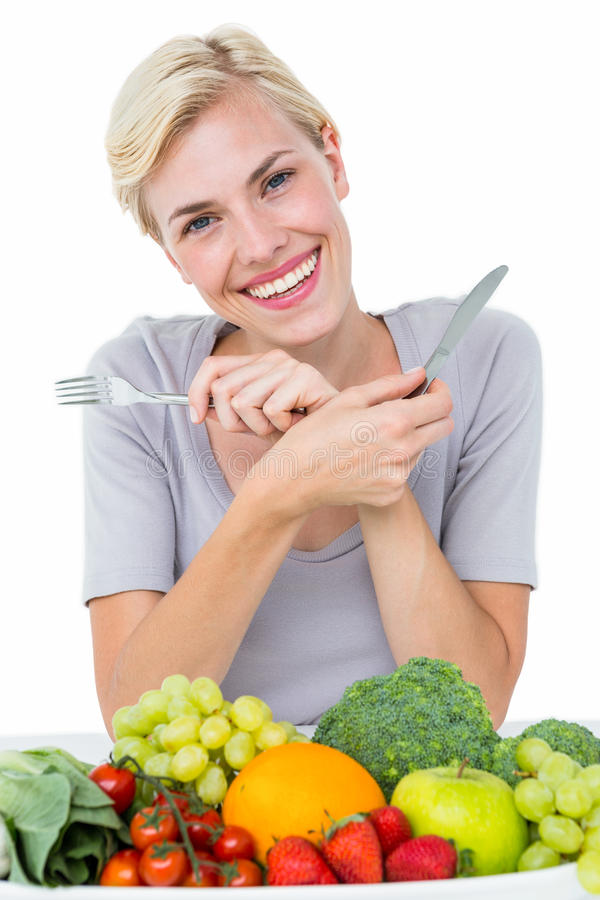 Mujer rubia feliz que se sienta sobre la comida sana foto de archivo