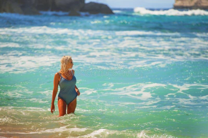 Mujer rubia feliz y atractiva joven en traje de baño de una pieza en el agua que mira el mar en playa tropical hermosa imponente fotos de archivo libres de regalías