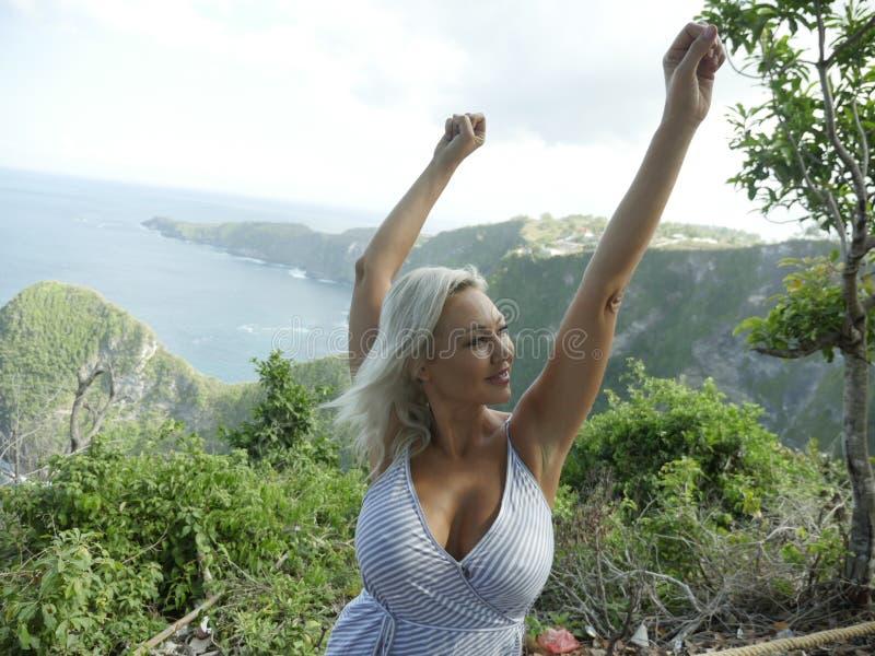 Mujer rubia feliz y hermosa joven relajada en el paisaje tropical del acantilado de la playa que disfruta de la partida de las va fotos de archivo