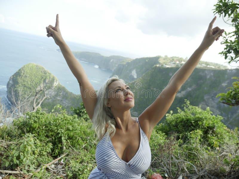 Mujer rubia feliz y hermosa joven relajada en el paisaje tropical del acantilado de la playa que disfruta de la partida de las va imagenes de archivo
