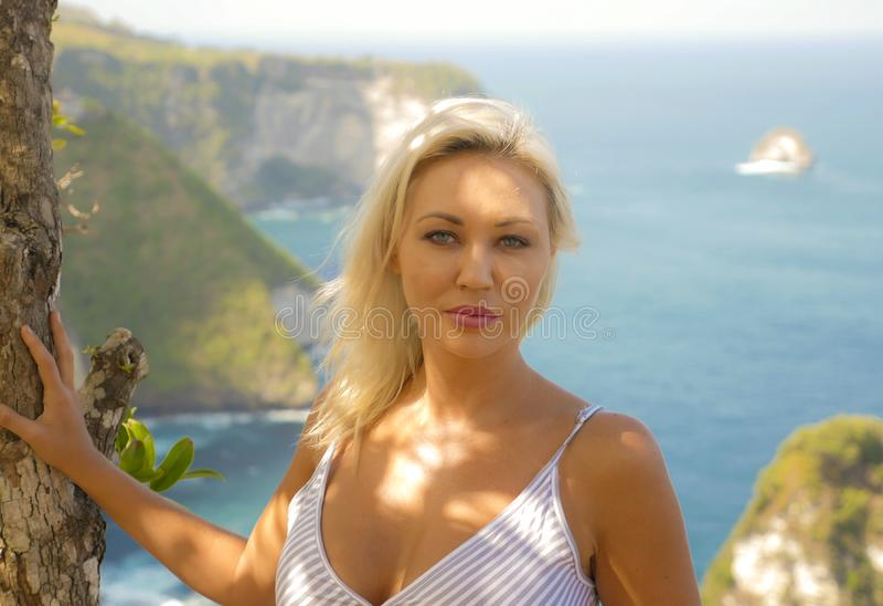Mujer rubia feliz y hermosa joven relajada en el paisaje tropical del acantilado de la playa que disfruta de la partida de las va foto de archivo