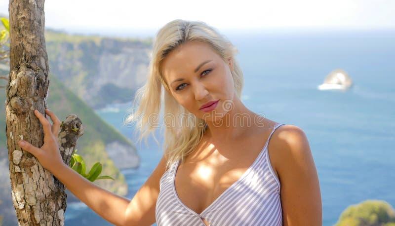 Mujer rubia feliz y hermosa joven relajada en el paisaje tropical del acantilado de la playa que disfruta de la partida de las va foto de archivo libre de regalías