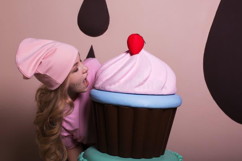 Mujer rubia hambrienta que lleva el casquillo rosado que goza de la magdalena grande en el estudio imagenes de archivo