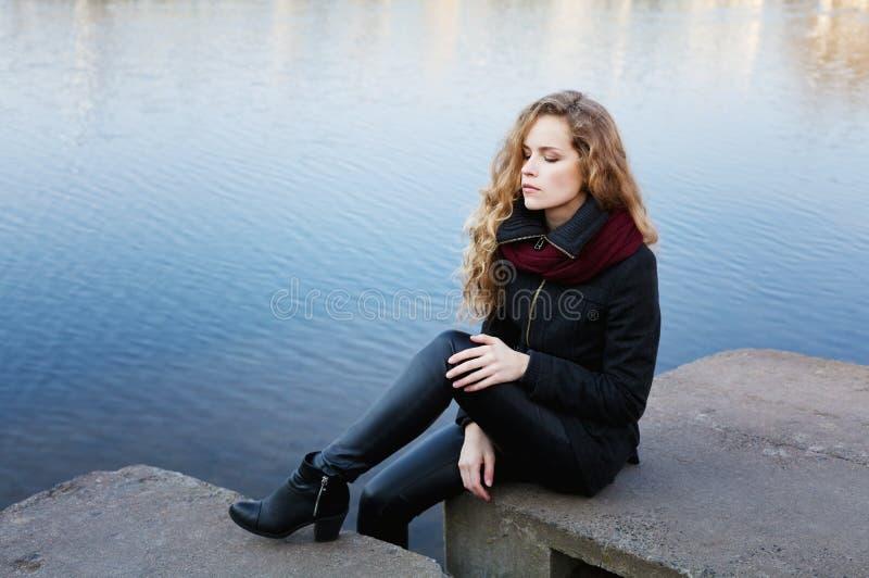 Mujer rubia hermosa con el pelo rizado largo que se sienta en los bancos del agua de río azul imagen de archivo libre de regalías