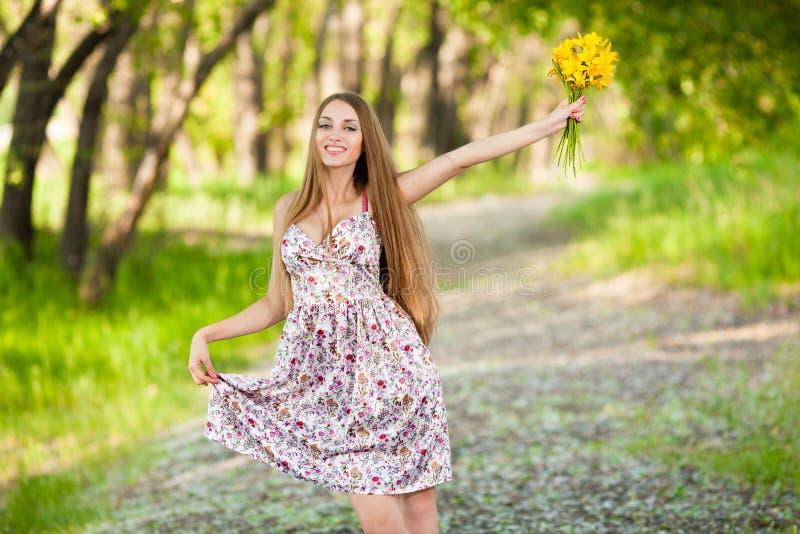 Mujer rubia hermosa con las flores amarillas al aire libre imagen de archivo libre de regalías