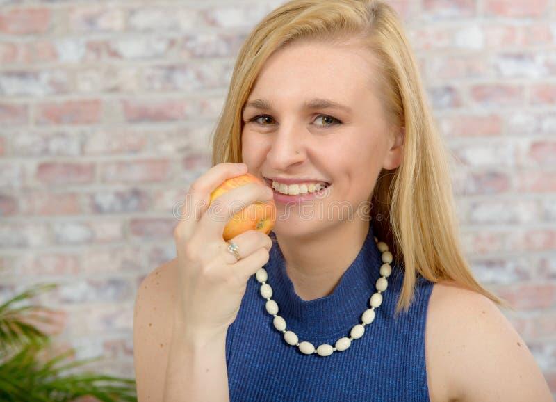 Mujer rubia hermosa con un suéter azul que come la manzana foto de archivo