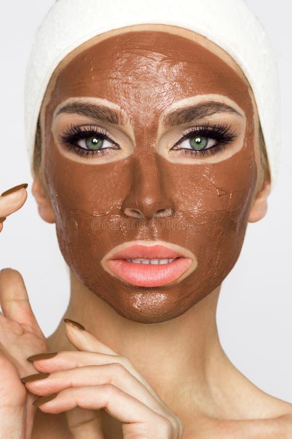 Mujer rubia hermosa con una máscara facial, balneario de la belleza Mascarilla del chocolate foto de archivo libre de regalías
