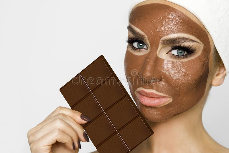 Mujer rubia hermosa con una máscara facial, balneario de la belleza Mascarilla del chocolate fotografía de archivo libre de regalías