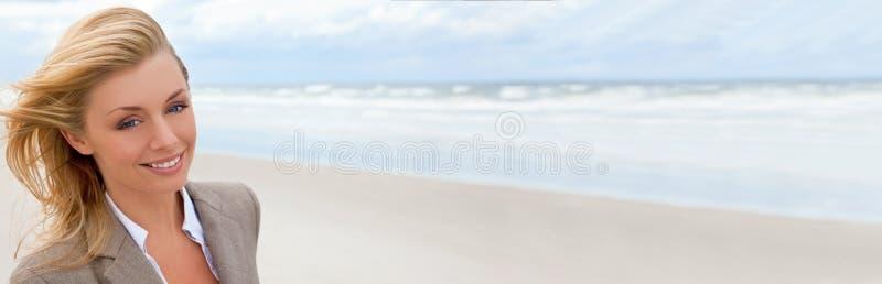 Mujer rubia hermosa de la bandera panorámica de la web en la playa foto de archivo