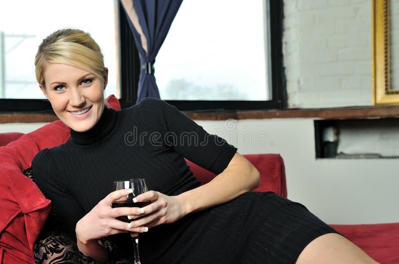 Mujer rubia hermosa en alineada negra con el vino foto de archivo