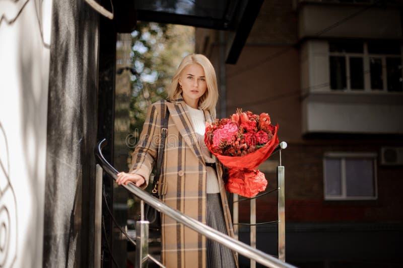 Mujer rubia hermosa en capa de la tela escocesa con un ramo rojo grande de f imagen de archivo libre de regalías