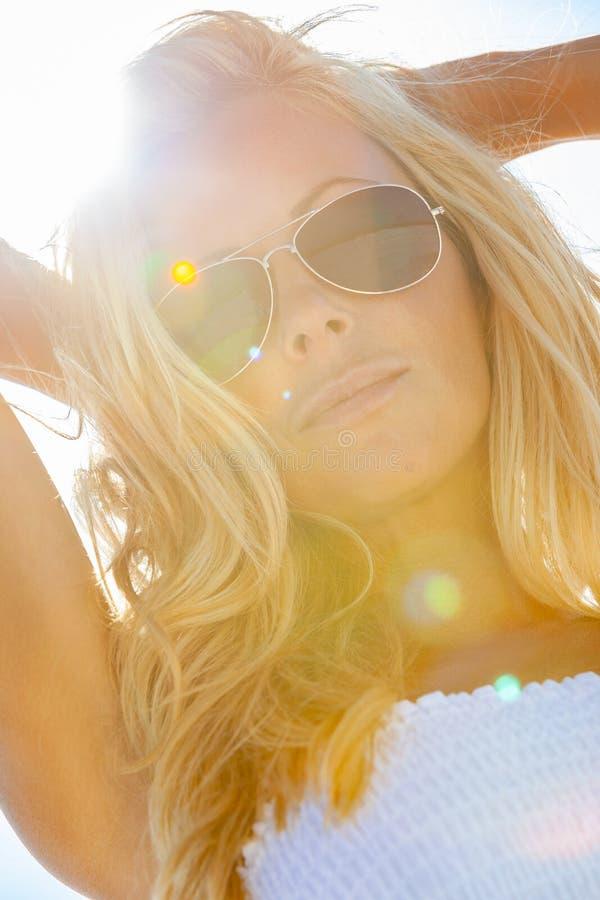 Mujer rubia hermosa en el vestido y las gafas de sol blancos en la playa fotografía de archivo libre de regalías