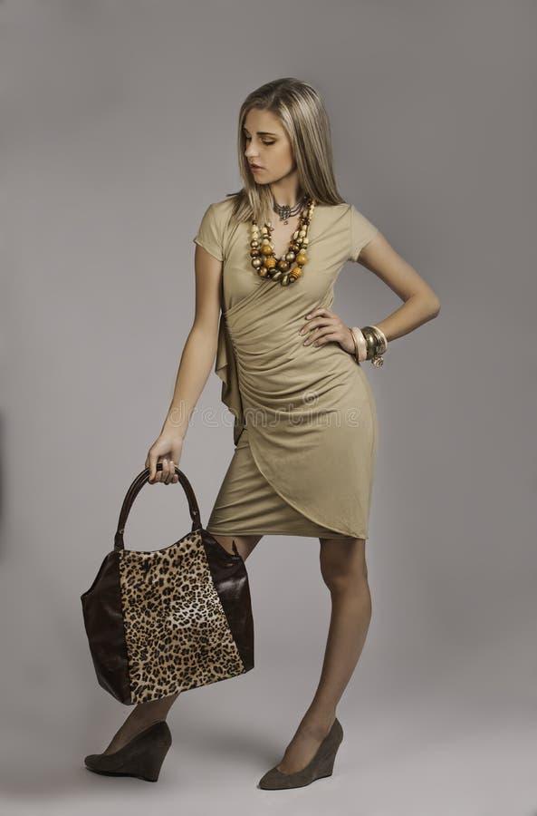 Mujer rubia hermosa en equipo elegante del safari con el bolso del estampado de animales foto de archivo