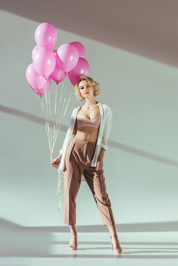 mujer rubia hermosa en ropa elegante y sujetador que presenta con los globos rosados y que mira la cámara fotografía de archivo libre de regalías