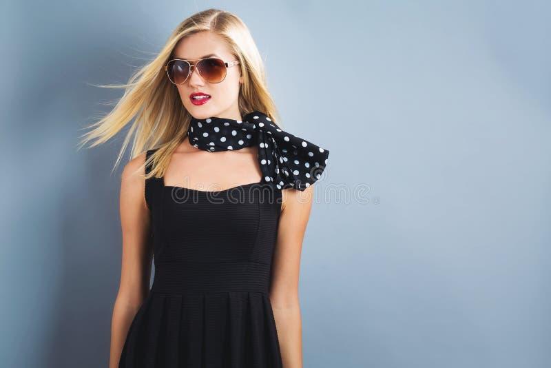 Mujer rubia hermosa en un vestido negro imagen de archivo libre de regalías