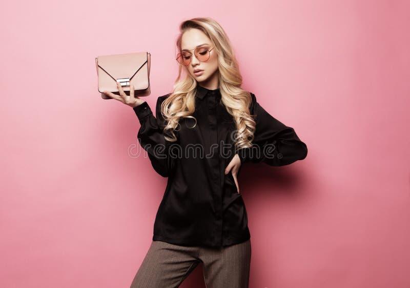 Mujer rubia hermosa en una blusa y los pantalones que llevan los vidrios, sosteniendo el bolso que presenta sobre fondo rosado fotos de archivo