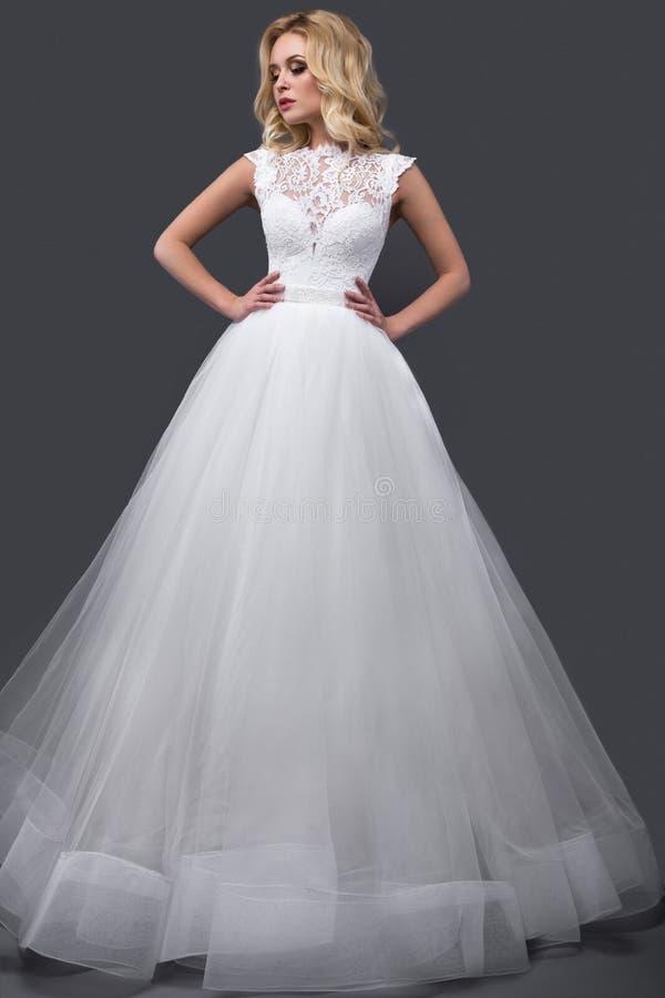 Mujer rubia hermosa en vestido de boda con maquillaje de la tarde, labios blandos y rizos Imagen de la novia Cara de la belleza imagenes de archivo