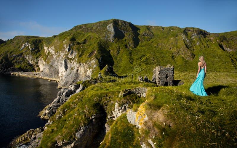 Mujer rubia hermosa en vestido largo verde de la turquesa, en la orilla de mar al lado de una ruina medieval en Irlanda fotos de archivo
