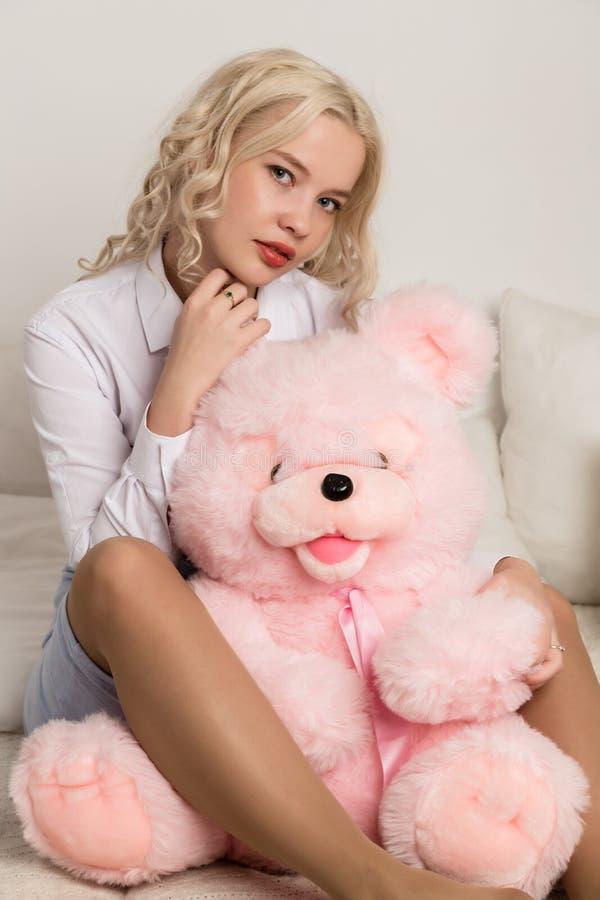 Mujer rubia hermosa feliz que abraza un oso de peluche Concepto de día de fiesta o de cumpleaños foto de archivo libre de regalías