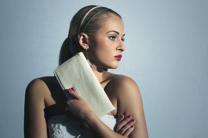 Mujer rubia hermosa Gente de la manera Muchacha con estilo Compras Novia con el embrague blanco imagen de archivo libre de regalías