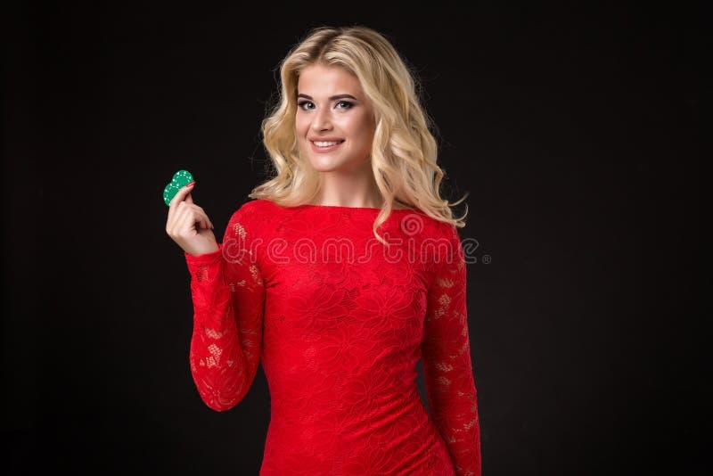 Mujer rubia hermosa joven con las fichas de póker sobre negro póker imagen de archivo