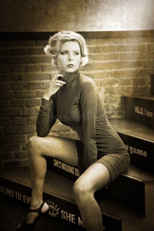 Mujer rubia hermosa joven del pelo corto en del cuello cisne el vestido que se sienta en las escaleras, foto blanco y negro del c foto de archivo libre de regalías