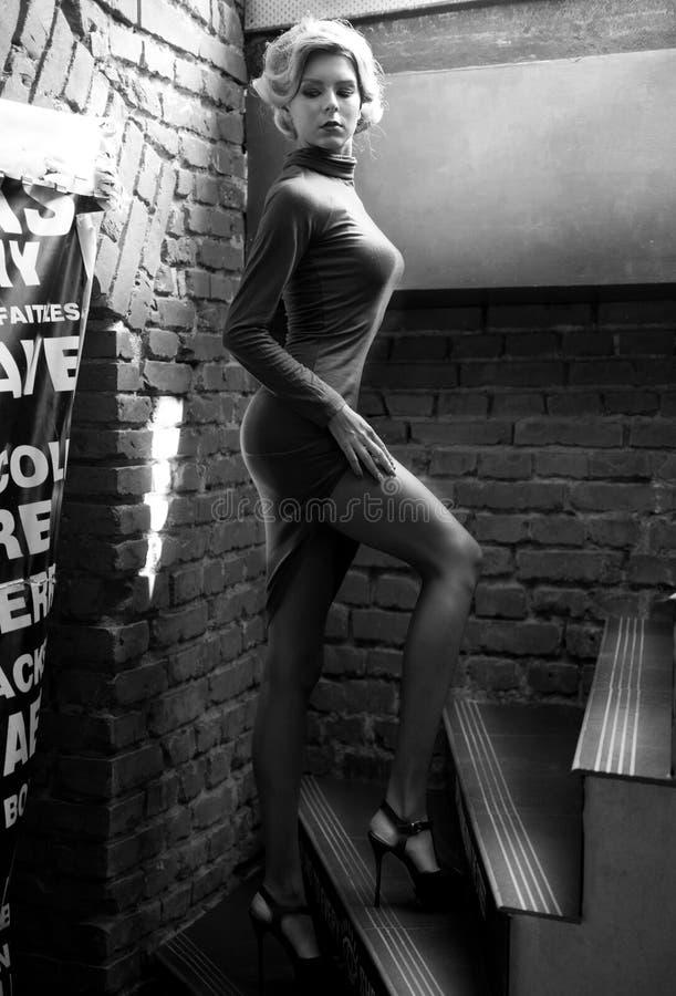 Mujer rubia hermosa joven del pelo corto en el negro que sube las escaleras, foto blanco y negro Vista lateral de la muchacha rom imagen de archivo
