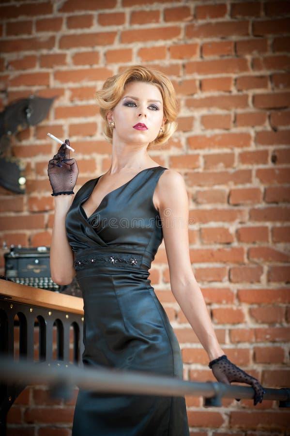 Mujer rubia hermosa joven del pelo corto en el vestido negro que fuma un cigarrillo Señora misteriosa romántica elegante con mira fotografía de archivo libre de regalías